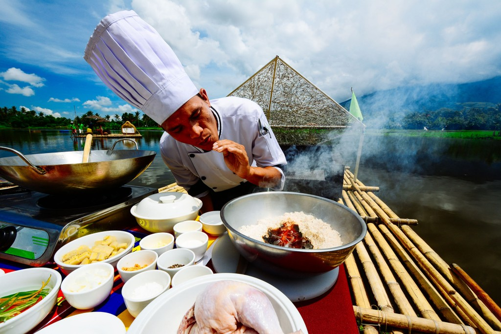 Cooking tinutungang manok (chicken cooked in burnt coconut cream) on Sumlang Lake with Mt. Mayon as backdrop