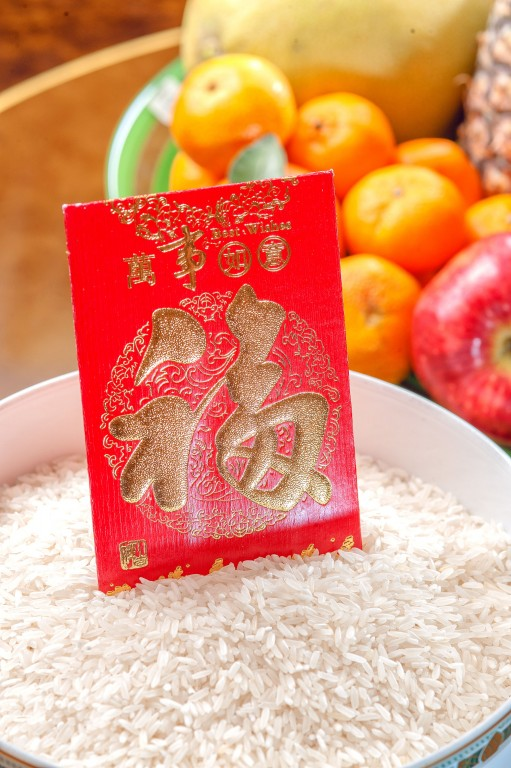 A must on New Year's eve: A container full of rice with an angpao (red envelope) containing Php168. By Jeffrey Sonora