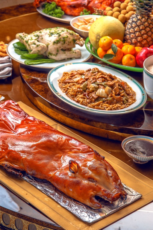 It's a feast! Roast whole pork, whole chicken and fruits should be on the table on the eve of Chinese New Year to attract lady luck. By Jeffrey Sonora