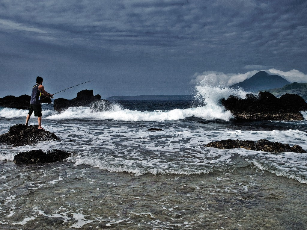 Chip Childers tries his hand at fishing in Mabutay. In the background is Mt. Iraya. Photo by Ferdz Decena
